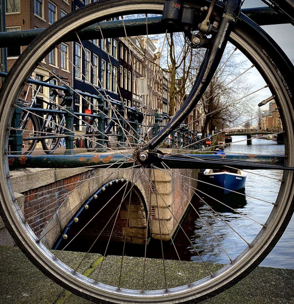Bicycle Wheel and Canal, Amsterdam, Netherlands. Photo by Arnold Plotnick